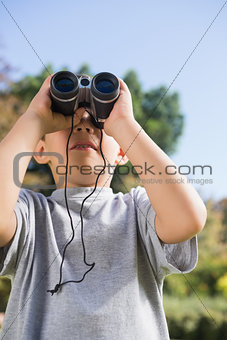 Boy looking through binoculars to the sky
