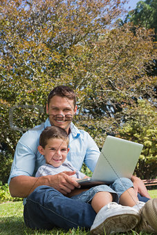 Attractive dad and son smiling in a park