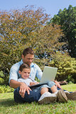 Cheerful dad and son with a laptop