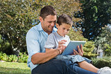 Dad and son using a tablet pc in a park