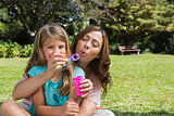 Smiling daughter with mother making bubbles