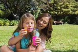 Daughter blowing bubbles with mother