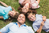 Happy family lying on the grass in a circle