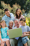 Happy multi generation family with a laptop sitting in park