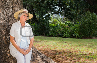 Thoughtful retired woman sitting on tree trunk