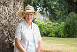 Cheerful retired woman sitting on tree trunk