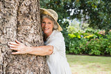 Retired woman hugging a tree smiling at camera