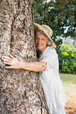 Retired woman hugging a tree and smiling