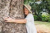 Happy older woman hugging a tree