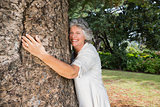 Smiling older woman hugging a tree