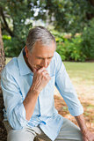 Thoughtful retired man sitting on tree trunk with head bowed