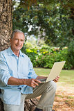 Old man leaning against tree with a laptop