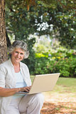 Happy mature woman using a laptop sitting on tree trunk