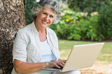 Cheerful mature woman using a laptop sitting on tree trunk
