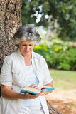 Cheerful mature woman reading book leaning on tree trunk