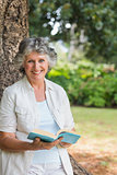 Smiling mature woman reading book leaning on tree trunk