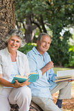 Happy older couple reading books together sitting on tree trunk looking at camera