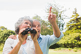 Man showing something to his wife holding binoculars