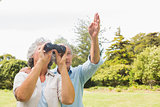 Man pointing to something for his wife holding binoculars