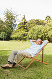 Happy mature man resting in sun lounger