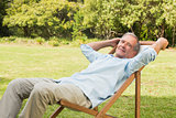 Happy mature man sitting on sun lounger