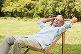 Happy mature man sitting on sun lounger