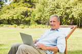 Happy mature man using laptop
