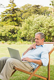 Man using laptop on sun lounger