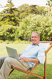 Smiling mature man using laptop