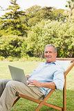 Smiling mature man using laptop