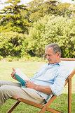 Happy mature man reading book