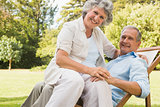 Happy mature woman sitting on her husband on deck chair