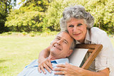 Smiling mature woman standing behind her husband on deck chair