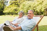 Happy mature couple sitting on sun loungers