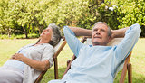 Relaxing mature couple sitting on sun loungers