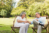 Relaxing mature couple sitting on sun loungers and talking