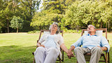 Mature couple relaxing on sun loungers