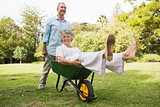 Happy man pushing his laughing wife in a wheelbarrow