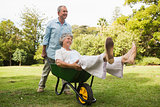 Smiling man pushing his wife in a wheelbarrow
