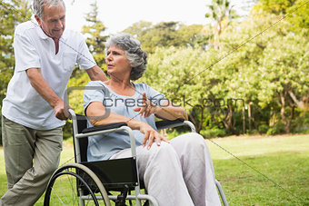 Mature woman in wheelchair speaking with partner
