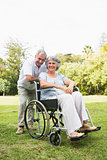 Happy mature woman in wheelchair with partner