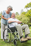 Cheeful mature man in wheelchair with partner