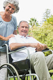Cheerful mature man in wheelchair with partner