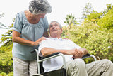 Cheerful mature man in wheelchair talking with partner