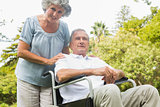 Cheerful mature man in wheelchair with his partner
