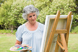 Content mature woman painting on canvas