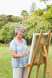 Happy retired woman painting on canvas