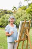 Cheerful retired woman painting on canvas