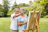 Content retired woman painting on canvas with husband