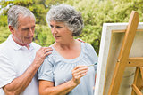 Cheerful retired woman painting on canvas and talking with husband